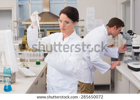 Scientists working attentively with test tube and microscope in laboratory - stock photo