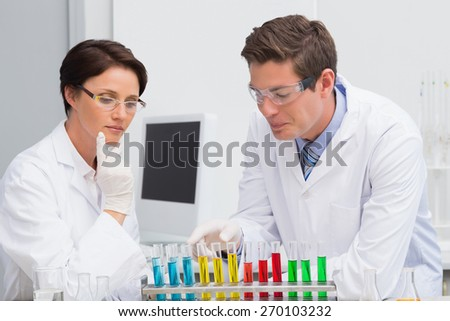 Scientists working attentively with test tube in laboratory - stock photo