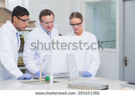 Scientists working on computer together on the laboratory - stock photo