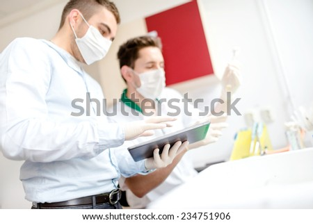 Scientists working on tablet in laboratory with experiments and tools - stock photo
