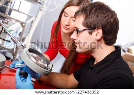 Scientists working with magnifier - stock photo