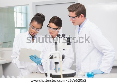 Scientists working with microscope and taking notes in laboratory - stock photo