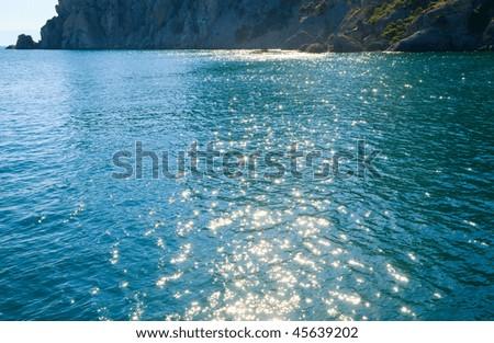 "Scintillate sea surface and summer rocky coastline  (""Novyj Svit"" reserve, Crimea, Ukraine). - stock photo"