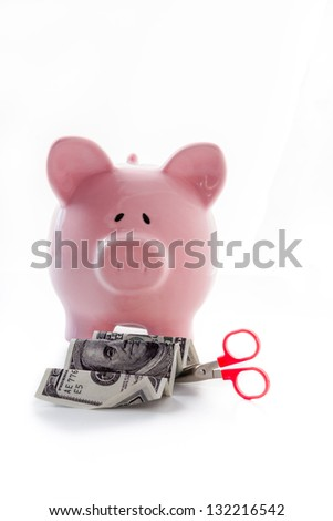 Scissor cutting dollar note in front of piggy bank on white background - stock photo