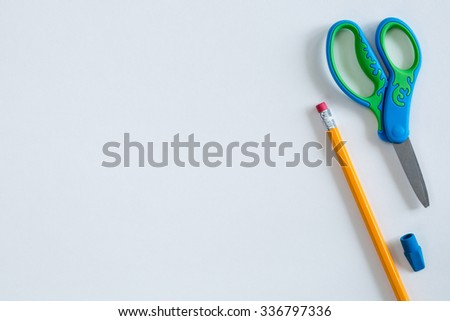 Scissors, a pencil, and an eraser placed in a pleasing way on white paper to create a border for multiple purposes. Can be used as a horizontal or vertical format or it can even be flipped and rotated - stock photo