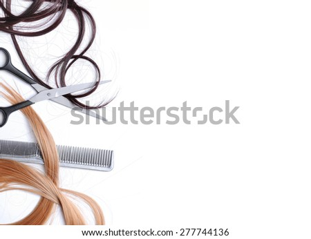 Scissors and comb with brown and blond hair to the left of the image with space to write text, isolated white, top view - stock photo