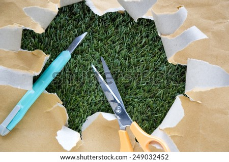 scissors and cutter on torn paper with green grass background - stock photo