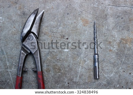 Scissors and drill on wooden desk, construction office, vintage workshop