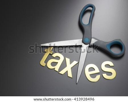 scissors and the alphabet TAXES - stock photo