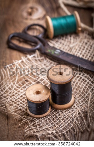 Scissors, bobbins with thread and needles on the old wooden table. - stock photo