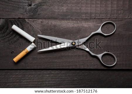 Scissors cut a cigarette on a black table - stock photo