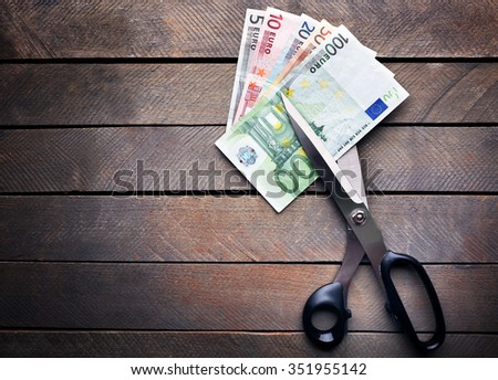 Scissors cut euro banknotes on wooden background - stock photo