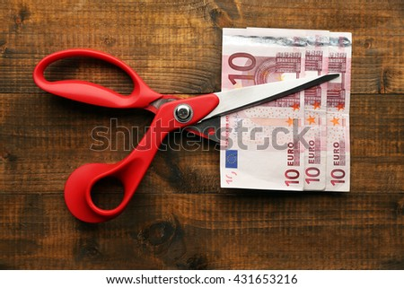 Scissors cuts euro banknote on wooden background - stock photo