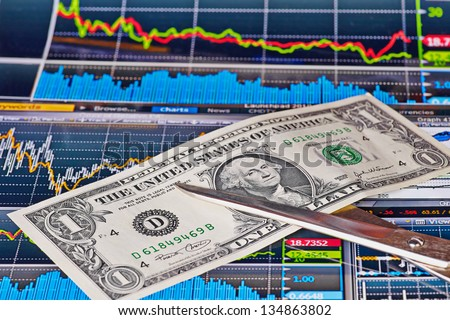 Scissors cuts US one-dollar banknote, financial chart as background. Selective focus - stock photo