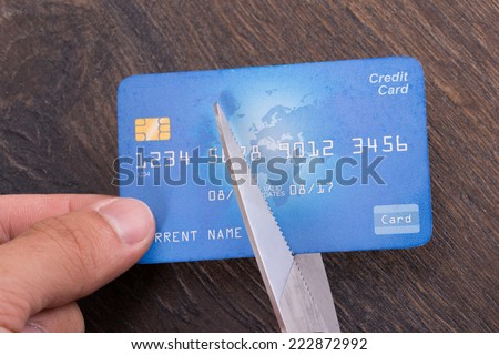 Scissors cutting old credit card. Closeup shot