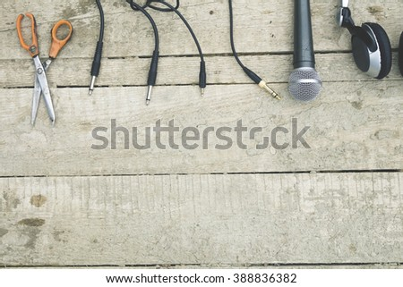 Scissors four plug microphone, headset on an old wooden surface - stock photo