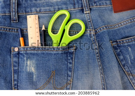 Scissors ruler and pencil in  the blue jeans back pocket  - stock photo