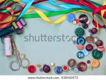 scissors, thread, needle, thimble, buttons and variety silk ribbon on old gray cardboard table - stock photo