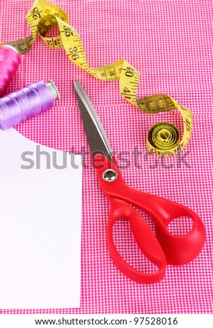 Scissors,threads, measuring tape and pattern on fabric close-up - stock photo