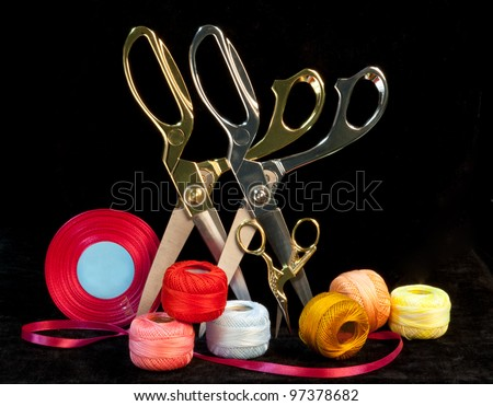 Scissors with a ribbon on a dark background - stock photo
