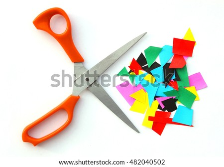 Scissors with scrap colorful paper and white background.