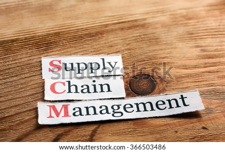 SCM Supply Chain Management acronym on  paper on wooden background