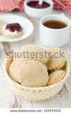 Scone of whole wheat in a wicker basket for breakfast vertical - stock photo