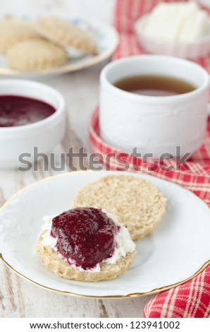 Scone with goat cheese and jam, cup of tea for breakfast closeup - stock photo