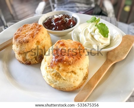 Scone with raspberry jam and whipping cream. High tea set.