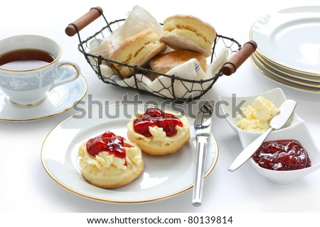 scone with strawberry jam and clotted cream , afternoon tea break , cream tea , tea party , buttermilk biscuits