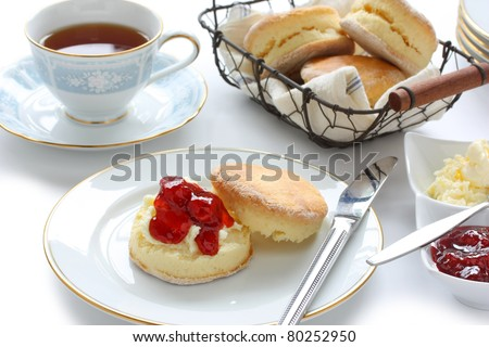 scone with strawberry jam and clotted cream , cream tea , devonshire tea , tea party , afternoon tea , buttermilk biscuits - stock photo