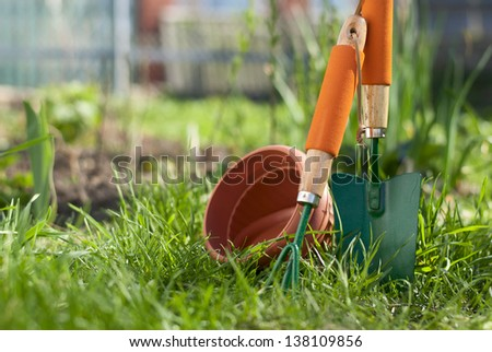 scoop, fork, and clay pots and in the garden on the lawn