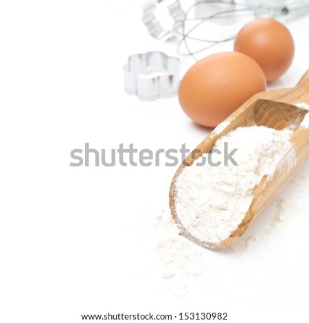 scoop with flour, eggs and cookie cutters isolated on white - stock photo