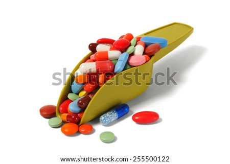 Scoop with pills isolated on white background