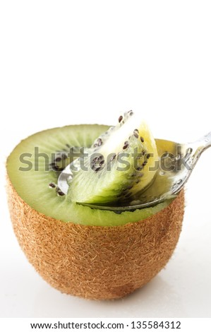 Scooping Kiwi fruits with spoon on white background
