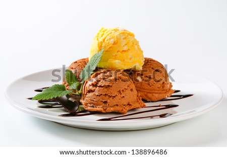 Scoops of chocolate and vanilla ice cream on a plate - stock photo