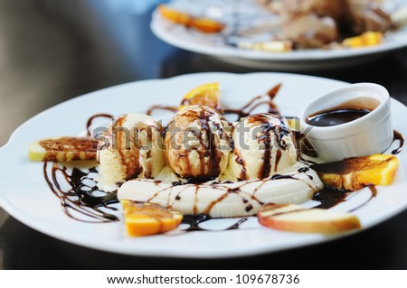 Scoops of coffee ice-cream with chocolate syrup and orange on white plate - stock photo