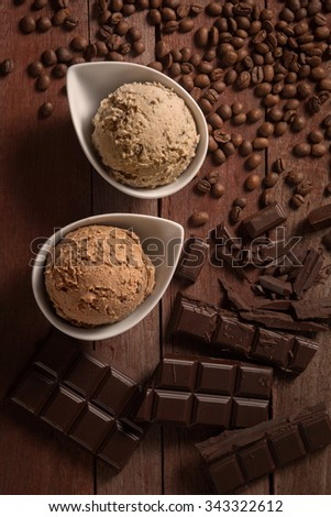 scoops of ice cream, chocolate and coffee on wooden background - stock photo
