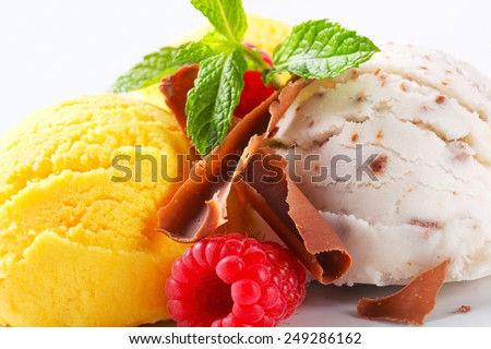Scoops of ice cream with chocolate curls and fruit - stock photo
