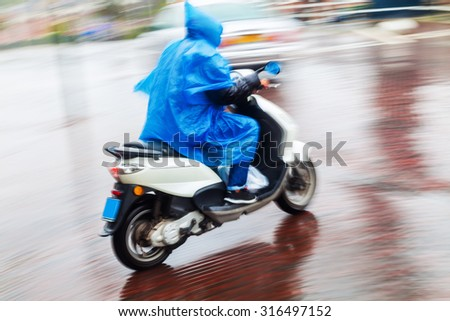 scooter rider in a blue cape on the move in the rainy city in motion blur - stock photo