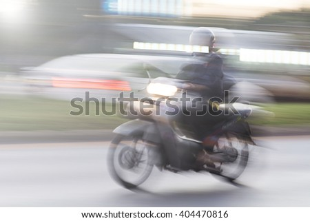 scooter rider on a bike lane in the busy city traffic in motion blur - stock photo