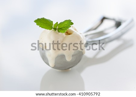 Scope of homemade vanilla ice cream in a metal spoon with fresh mint, closeup, horizontal - stock photo