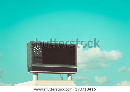 score board at football stadium with bluesky , vintage tone - stock photo
