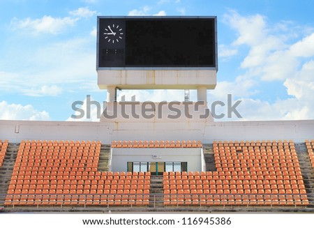 Scoreboard, orange seat in stadium with cloud and blue sky backg - stock photo