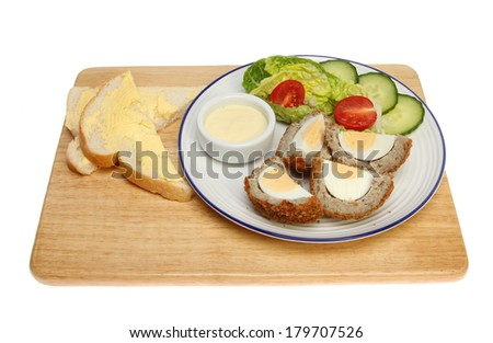 Scotch egg and salad with bread and butter on a wooden board isolated against white - stock photo