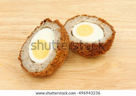 Scotch egg cut in half on a wooden chopping board