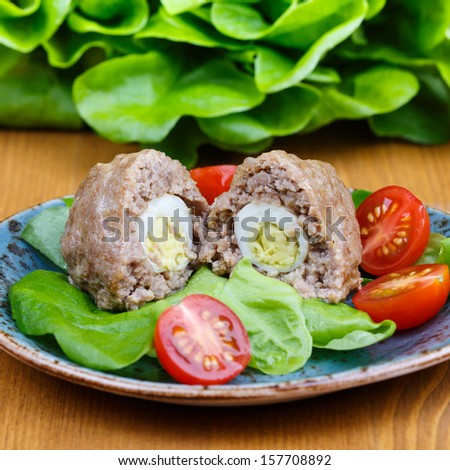 Scotch eggs on a plate with a green salad and tomatoes - stock photo