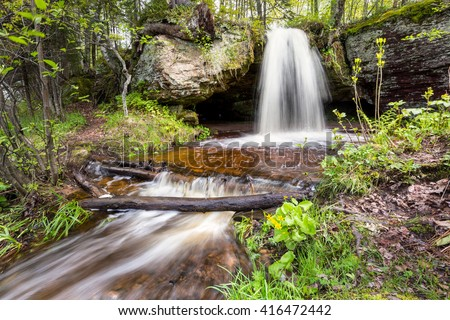 Scott Falls near Au Train Michigan. Surrounded by marsh marigolds, in the spring season,  this little roadside waterfall is in the Upper Peninsula. - stock photo
