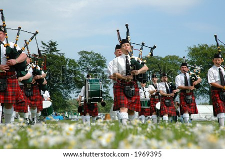 Scottish band marching on grass - stock photo