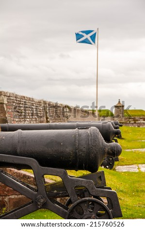scottish flag flies over cannons at fort george, scotland - stock photo
